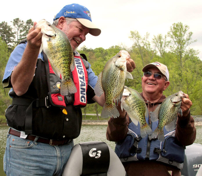 Rich and Dickie holding up four fat Crappie caught on Road Runners on Truman Lake